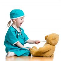 Child pracitcing safely feeding medicine to her teddy bear