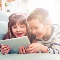 Happy siblings lying on sofa at home and playing with pc tablet together