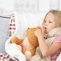 Little girl coughing holding her teddy bear