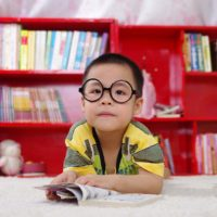 boy with eyeglasses in front of bookshelf