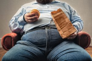 overweight man eating burger