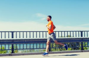 Smiling young man with heart rate watch running at summer seaside