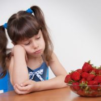 Girl sadly looks at the plate with strawberries