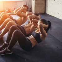 adults doing situps in a studio