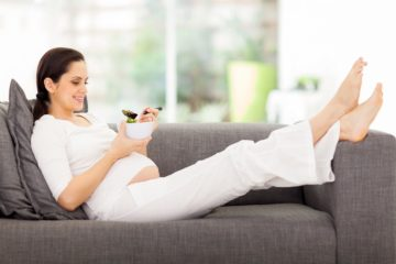 Prenant lady lying on couch eating foot and trying to avoid contracting lysteria