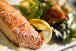 Seared salmon on a plate with fresh salad and lemon
