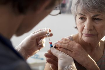 Elderly lady having the shingles vaccine administered by a doctor