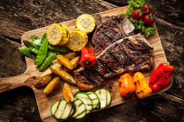Delicious steakhouse porterhouse steak and colorful fresh roast vegetables, view from above
