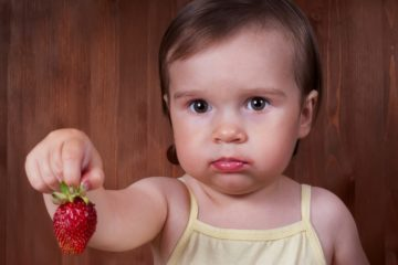 Toddler holding out a strawberry and upset because of allergy