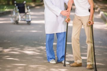 Close-up of doctor helping to his patient with osteoporosis to walk with crutches