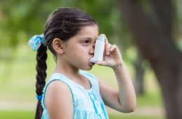 Little girl using her asthma inhaler on a sunny day