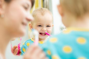 Infant with baby teeth learning how to brush