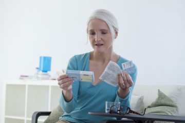 Mature lady reading the instructions to her hormone replacement therapy tablets