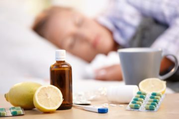 Vitamins, medicines and hot tea in front of woman with a cold sleeping in background
