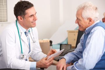 A general practitioner talking to senior man in his practice surgery