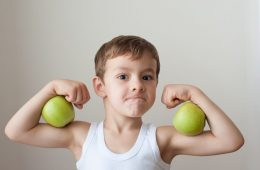 Boy with green apples showing biceps after strength training