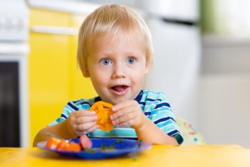 Cute young boy eating fresh vegetables