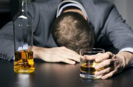 Drunk businessman holding a glass of whiskey