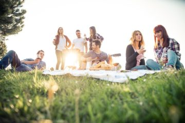 Group of friends relaxing on the grass in the summeritme having a good time together