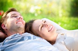 Happy Smiling Couple Relaxing on Green Grass in the Park