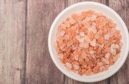 Himalayan rock salt in a bowl over wooden background