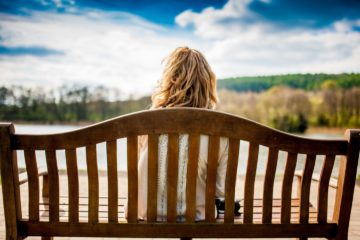 Lonely blonde lady sat on park bench along looking out a lake