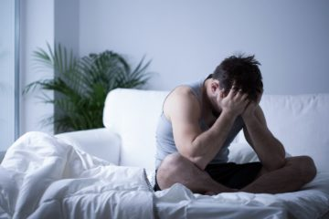 Man with depression sat on bed with head in his hands
