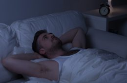 Man with insomnia looking at the ceiling instead of sleeping