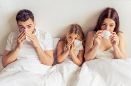 Parents and their daughter suffering from a cold wiping noses while lying on bed