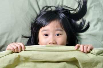 Scared little asian girl having childhood nightmares and hiding behind blanket