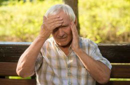Senior man holding his head because he is having a stroke and needs to call an ambulance