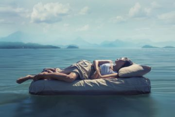 Sleeping woman lies on airbed floating on a lake