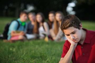 Teenage boy feeling sad being watched by a group of friends in the background