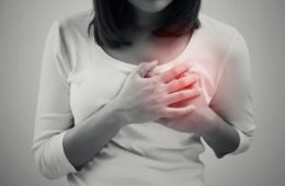 Woman is clutching her chest in acute pain caused by heart disease