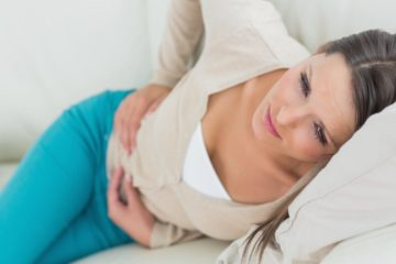 Woman lying on the bed suffering from a bad stomach bug