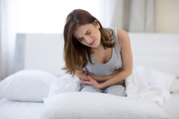 Woman sat on bed feeling constipated