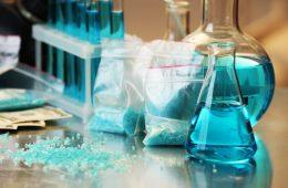 Blue methamphetamine and liquid in flasks on table in laboratory