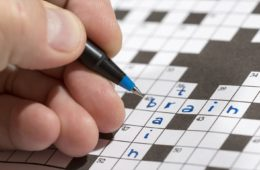 Man is holding a pencil in his hand and there are words 'train' and 'brain' already written in the crossword
