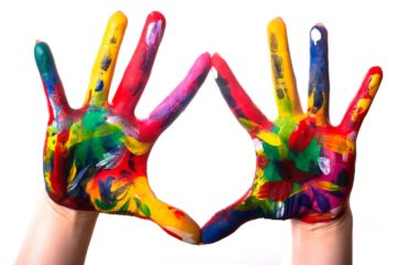 Rainbow coloured hands held up in front of a white background