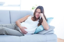 Sad pregnant woman lying on sofa suffering from depression