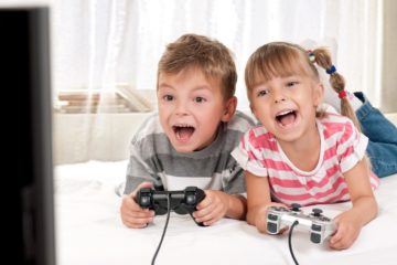 Young boy and girl lying on a bed enjoying playing video games together