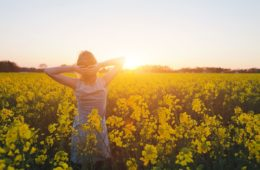 Woman enjoying summer and nature in yellow flower field at sunset harmony and healthy lifestyle