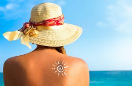 Woman with sunscreen avoiding skin cancer looking out to the ocean