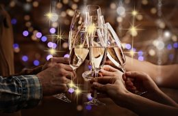 Clinking glasses of champagne in hands on bright lights background at Christmas