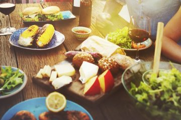 Group eating delicious food around the table in the summer sun