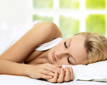 Woman lying on bed asleep enjoying some quality rest