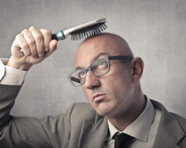 Bald man trying to brush his hair