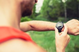 Man interval training on mountain forest trail checking looking at stopwatch smart watch