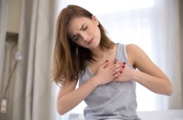 Young woman in pajamas having possible heart attack from heart disease