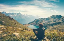 Man relaxing with serene view mountains and lake landscape